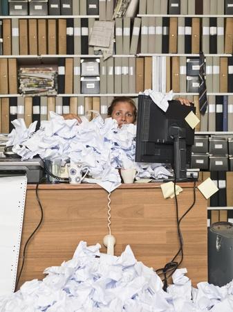 oficina desordenada: Empresaria sobrecargado con los papeles en la oficina desordenada