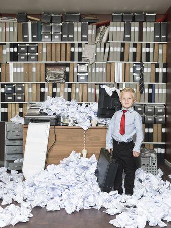 oficina desordenada: Chico joven como un hombre de negocios en una oficina desordenada