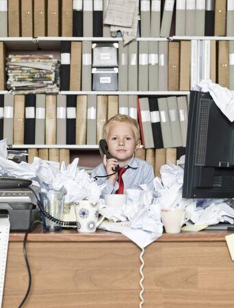 messy office: Giovane uomo d'affari al telefono in un ufficio disordinato