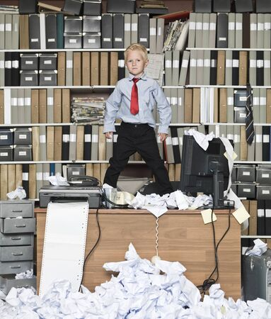 oficina desordenada: Joven empresario de pie sobre la mesa en una oficina desordenada