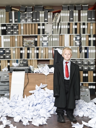 growing business: Young Businessman wearing oversized clothes in messy office Stock Photo