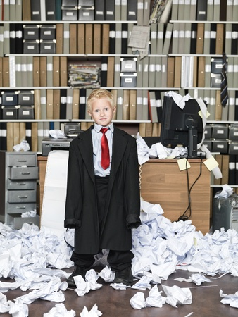 messy clothes: Young Businessman wearing oversized clothes in messy office Stock Photo
