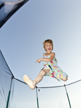 Young Girl Jumping in a trampoline photo