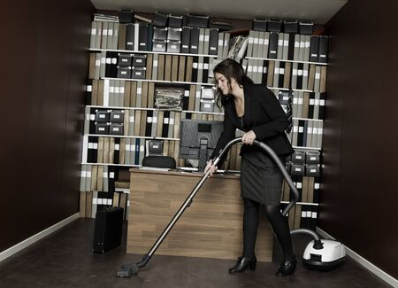 Young woman cleaning the office photo