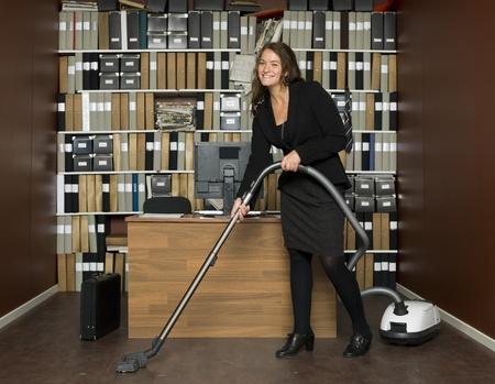 mujer limpiando: Mujer joven limpiando la oficina