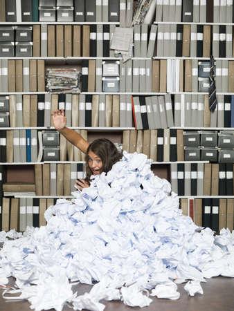 ahogarse: Mujer joven enterrado en papeles en la oficina Foto de archivo