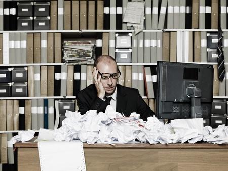 habitacion desordenada: Hombre de negocios cansado en una oficina desordenada
