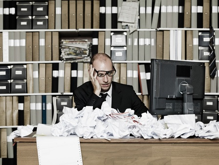 messy office: Tired Businessman at a messy office Stock Photo