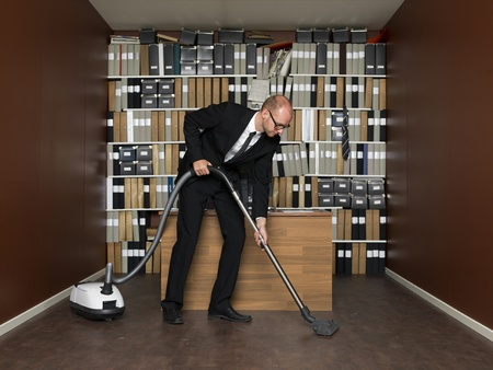 Young man with the vaacum cleaner at the office Stock Photo - 16711661