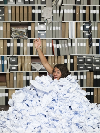 Young girl buried in papers at the office Stock Photo - 16711660