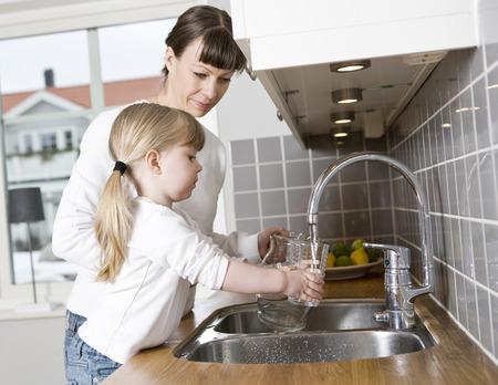 agua grifo: Pequeña Muchacha en la cocina con su madre el agua potable