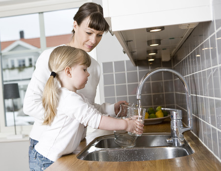 Small Girl in the kitchen with her mother drinking water photo