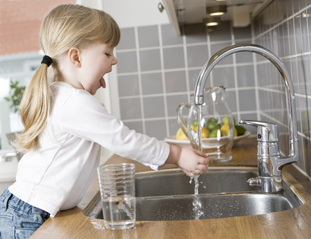 above water: Small Girl in the kitchen drinking water