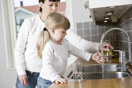 llave de agua: Pequeña Muchacha en la cocina con su agua potable de la madre Foto de archivo
