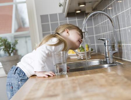 llave de agua: Pequeña muchacha en el agua potable de la cocina