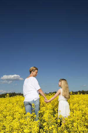 horizon over land: Mother and Daughter holding hands on a rape filed Stock Photo