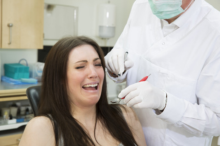 horrified: Afraid woman at the dentist Stock Photo