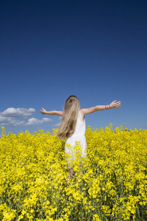 oilseed rape: Young girl with Outstretched arms on a Rape Field