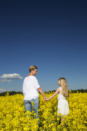 filed: Mother and Daughter holding hands on a rape filed Stock Photo