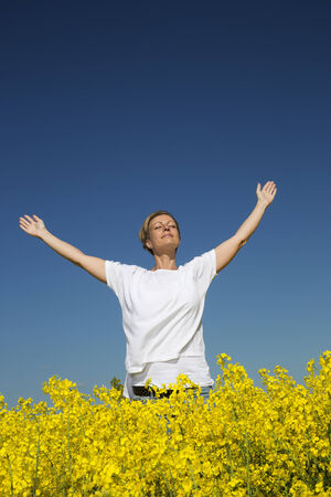 Smiling Woman with Outstretched arms on a Rape Field photo