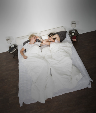 Angry wife and snoring man in the bedroom photo