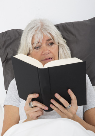electrifying: Mid age woman reading a nail-biting book in bed Stock Photo