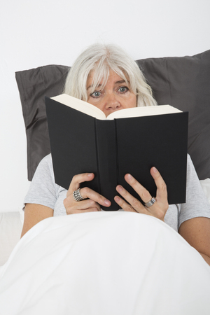 electrifying: Close up of a Mid age woman reading book in bed, from high angle view Stock Photo