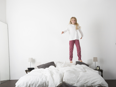 8 years: Happy Little Girl Jumping in bed with a smile on her face Stock Photo