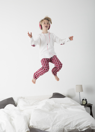 Happy Little Girl with Headphones jumping in bed photo