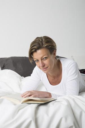 cabello corto: Mujer sonriente con el pelo corto de leer un libro en la cama