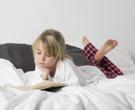 only girls: Young girl reading a book in bed