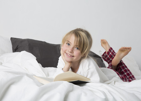 everyday scenes: Smiling Young Girl Reading a Book