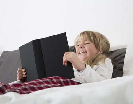 everyday scenes: Laughing Young girl reading a book in bed