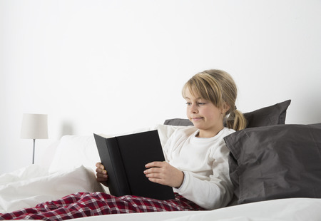 everyday scenes: Young girl reading a book in bed