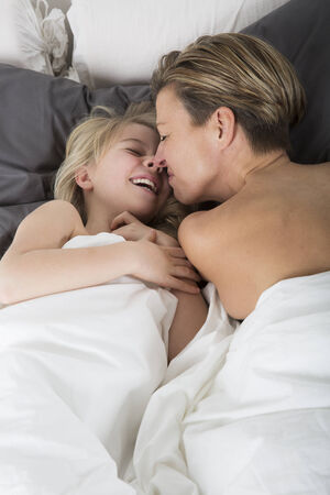 Mother and Daughter Bonding and smiling in bed photo