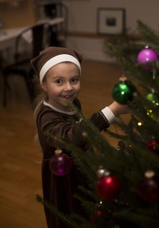 Happy Little Girl Hanging Decoration in a Christmas Tree photo