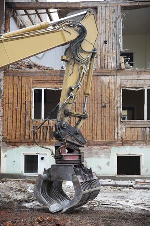 demolish: Close up of a Excavator demolish a House
