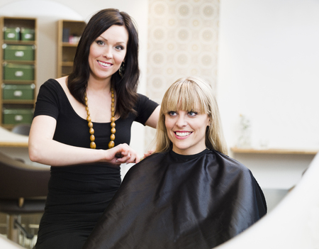 Hairdresser in action with blond customer photo