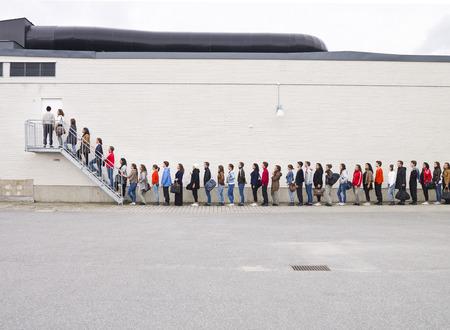 file d attente: Grand groupe de gens qui attendent en ligne Banque d'images