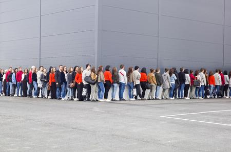 fila de personas: Grupo numeroso de personas esperando en línea