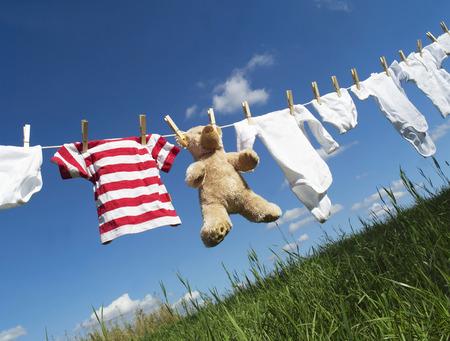 Babykleidung und ein Teddybär auf einer Wäscheleine gegen blauen Himmel Lizenzfreie Bilder