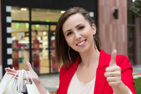 approved sign: Happy girl with thumb up show approved sign by hand in the city  Beautiful young woman holding shopping bags, showing the sign OK and smiling to camera in front of store
