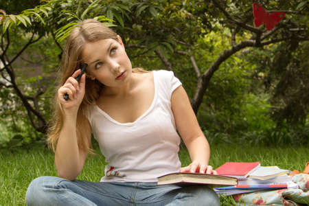 Portrait of college student with book thinking about exam photo