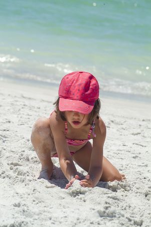 a young female playing in the sand while on vacation kids youngster girl 4 5 6 single 1 one alone play build beach sea ocean water hat cap color colour feel touch kneel holiday summer protect america usa florida gulf of mexico travel enjoy kids youth chil photo