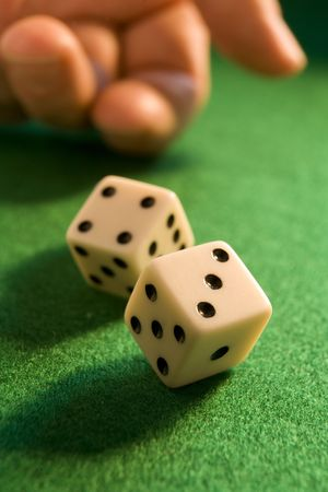 hand rolling dice onto a green baize Stock Photo