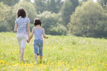 two girls walking away from camera in a field full of buttercups and dandelions with space for copy