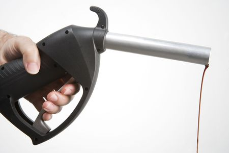 mans hand holding a petrol pump with a drip hanging from the end of the nozzle Stock Photo