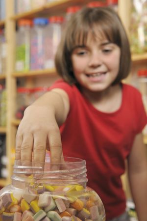 young girl grabbing sweets from a jar in a shop photo