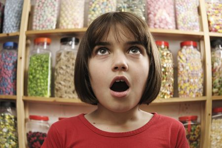 gape: young girl smiling in awe at rows of sweets