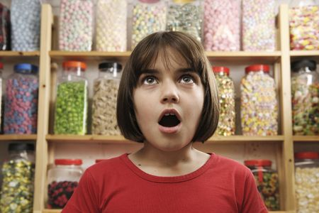 gape: young girl looking in awe at rows of sweets